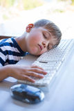 Little boy slipping on keyboard Stock Image