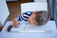 Little boy slipping on keyboard Royalty Free Stock Images