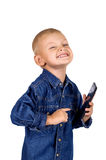 Little boy with smartphone. Portrait of a cute laughing little boy with smartphone in denim blue shirt isolated on white background Stock Photography