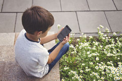 Little boy with smartphone sitting on stairs in city park. Technology, education and lifestyle concept Royalty Free Stock Images
