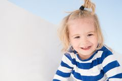 Little boy smile in navy clothes. Happy child enjoy sunny day. Kid smiling with blond hair ponytail. Kids fashion and style. Summe. R vacation, leisure and fun Royalty Free Stock Photos