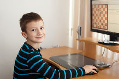 Little boy smile and play online chess. Little clever gamer at home Stock Image