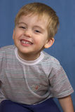 Little boy smiles. On blue background Stock Photos