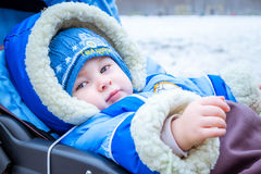 Little boy smiles. Funny baby in a carriage. Royalty Free Stock Photo