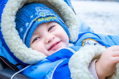 Little boy smiles. Funny baby in a carriage. Stock Image