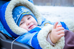 Little boy smiles. Funny baby in a carriage. Stock Photo