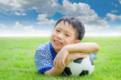 Little boy smiles with his football on field Stock Image