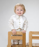 LITTLE BOY SMILING. STANDING ON THE CHAIR Stock Photo