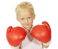 Little boy smiling with big boxing gloves. Blond Toddler with big red boxing gloves on smile self-satisfied Royalty Free Stock Photography