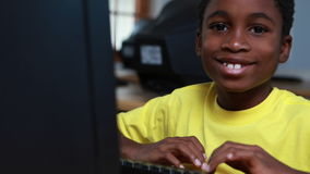 Little boy smiling at camera during computer class stock video footage