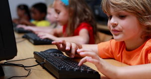 Little boy smiling at camera during computer class stock footage