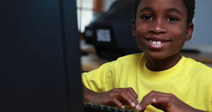 Little boy smiling at camera during computer class. In elementary school stock video