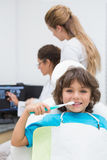 Little boy smiling at camera with mother and dentist in background Royalty Free Stock Photography