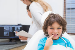 Little boy smiling at camera with mother and dentist in background Royalty Free Stock Photos