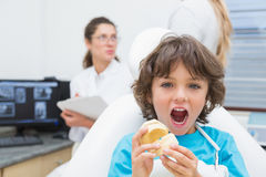 Little boy smiling at camera with mother and dentist in background Royalty Free Stock Image