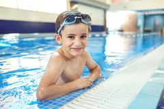 Little boy smiling child smiling at swimming pool indoors.  stock photo