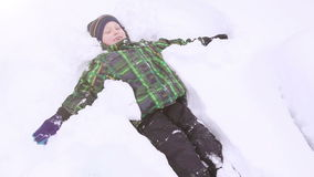 Little boy smiling and doing Snow angel stock video