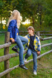 Little boy smiling and girl on fence looking at Royalty Free Stock Photography