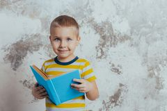 A little boy is smiling and holding a blue open book posing in front of a gray concrete wall stock photography