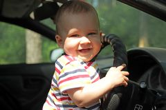 Little boy smiling holding the wheel of the car. stock photo