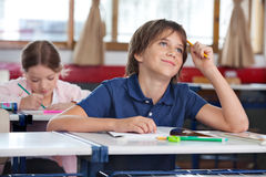 Little Boy Smiling While Looking Up In Classroom. Thoughtful little boy smiling while looking up with classmate in background at classroom Stock Photos