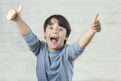Little boy smiling showing thumbs up stock photography