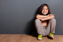 Little boy smiling and sitting on the wooden floor Stock Photos