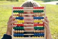 Little boy smiling thru an abacus. Little boy smiling thru the colorful abacus royalty free stock photos