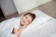 Little boy smiling during waking up in white bed Royalty Free Stock Images