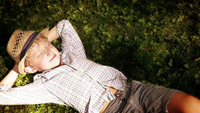 Little boy snoozes on the ground on the sunny afternoon under the tree stock video