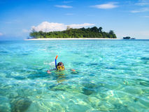 Little boy snorkeling next to tropical island. Young man snorkeling next to a beautiful tropical island Stock Photo