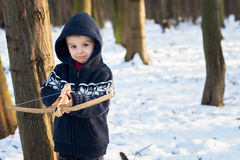 Little boy in the snow with crossbow Royalty Free Stock Images