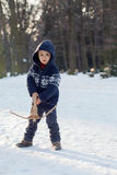 Little boy in the snow with crossbow Stock Images