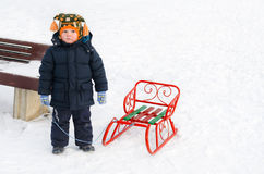 Little boy in the snow with his toboggan Royalty Free Stock Photos