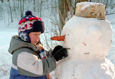 Little boy and snowman Stock Photos