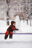 Little boy with snowman Stock Photos