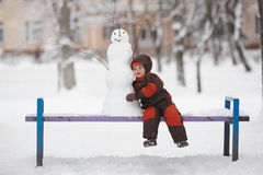Little boy with snowman Royalty Free Stock Images