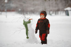 Little boy with snowman Stock Image