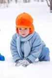 Little boy snowman sculpts. Little boy playing snowballs; snowman sculpts; digs snow Stock Photo
