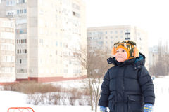 Little boy in a snowy urban winter landscape Royalty Free Stock Photo