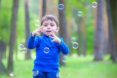Little boy with soap bubbles in summer park. Stock Photography