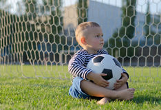 Little boy with a soccer ball on his lap. Little boy sitting in  goalposts with  soccer ball on his lap looking expectantly to  side as he waits for someone to Royalty Free Stock Photography