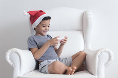 Little boy on the sofa playing on mobile Stock Photography