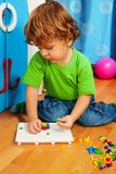 Little boy solving puzzle. Little two years old boy solving puzzle assembling mosaic sitting on the floor in his room Stock Photos