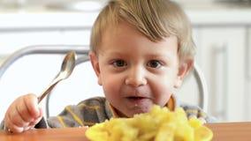 Little Boy som äter potatisar stock video