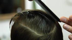 Little Boy som får frisyr av Barber While Sitting In Chair på frisersalongen stock video
