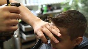 Little Boy som får frisyr av Barber While Sitting In Chair på frisersalongen lager videofilmer