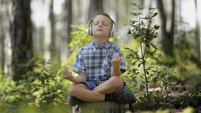 Little Boy som mediterar i skogen lager videofilmer