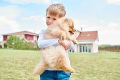 Little Boy som rymmer den älsklings- hunden Fotografering för Bildbyråer