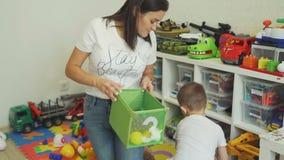Little Boy som sätter leksaker in i asken med hans moder lager videofilmer
